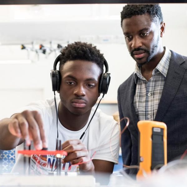 engineering student with headphones being observed by professor