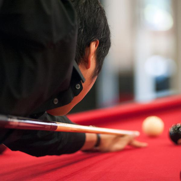 student lining up pool stick in eight ball game