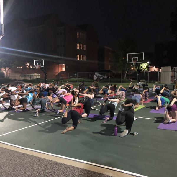 Students doing yoga outside on the basketball court