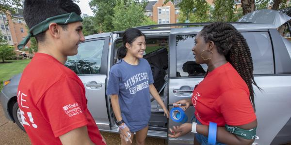 students outside greeting a new student moving in to the residence hall